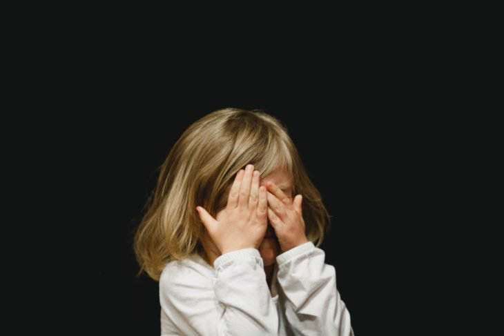 una niña rubia cubre su cara con sus manos sobre un fondo negro