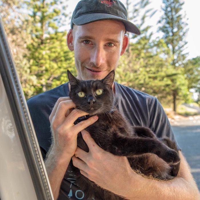 Rich sosteniendo al gato negro, Willow entre su sbrazos
