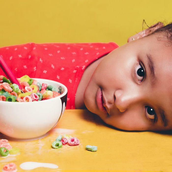 Una niña está recostada sobre la mesa en donde se observa un plato con cereal de colores