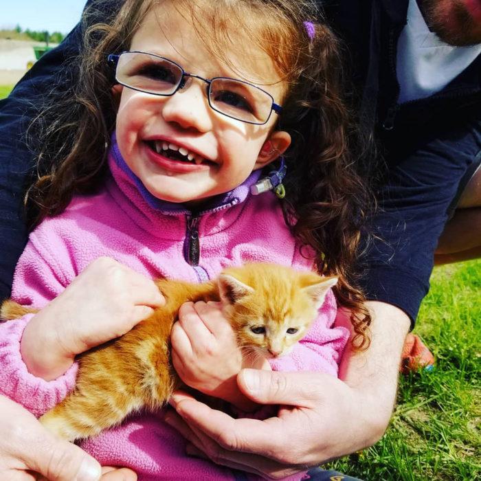 Morey Belanger con un pequeño gato en sus brazos y una persona abrazándola