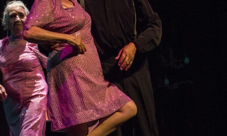 cuerpos de una pareja de adultos mayores baila tango, atrás de ellos otra mujer los observa