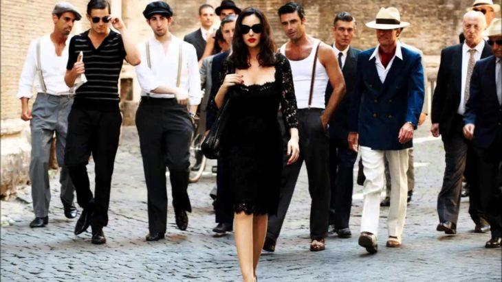 una mujer vestida de negro y con lentes oscuros es observada por varios hombres que la siguen