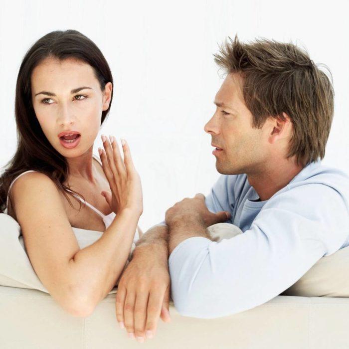 una mujer voltea hacia otro lado mientras su pareja le hablar de lado