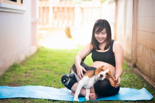 una mujer embarazada sentada en una manta en un jardín abraza a un beagle