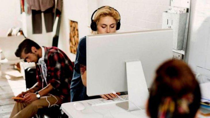 mujer trabaja frente a una computadora con audífonos puestos