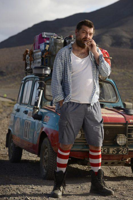 Escena de la película 4 latas. Hombre parado frente a un carro que tiene sus maletas