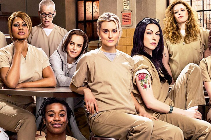 Escena de la serie de netflix orange is the new balck. Reclusas con el uniforme sentadas en el comedor