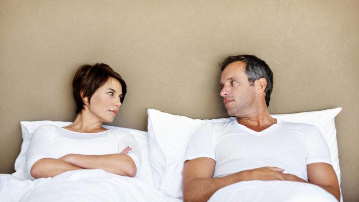 una pareja acostados en la cama se ven uno al otro