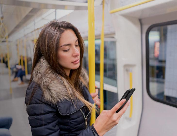 Mujer en el metro viendo su teléfono celular