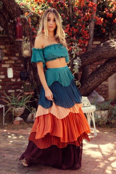 Faldas para el verano; chica de cabello largo y rubio con falda tableada en capas, de colores aqua, azul rey, salmón, anaranjado, rojo y morado; y un top campesino