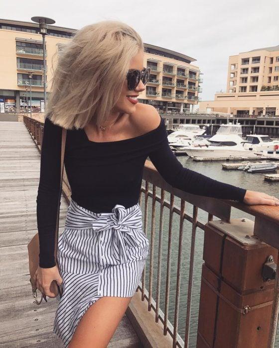 Faldas para el verano; chica rubia en el muelle con blusa sin hombros y falda rayada