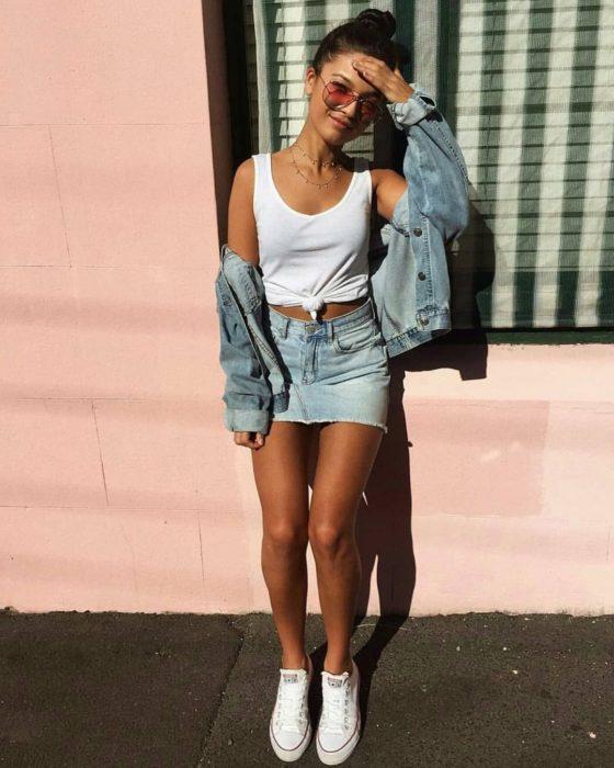 Faldas para el verano; chia recargada en la pared,con blusa sin mangas blanca, chaqueta y falda de mezclilla con tenis blancos