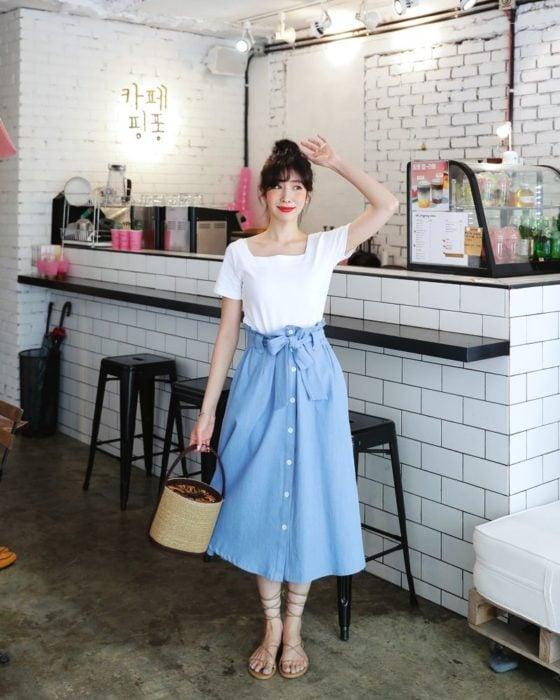 Faldas para el verano; chica con peinado de chongo, blusa básica blanca y falda denim larga, con sandalias