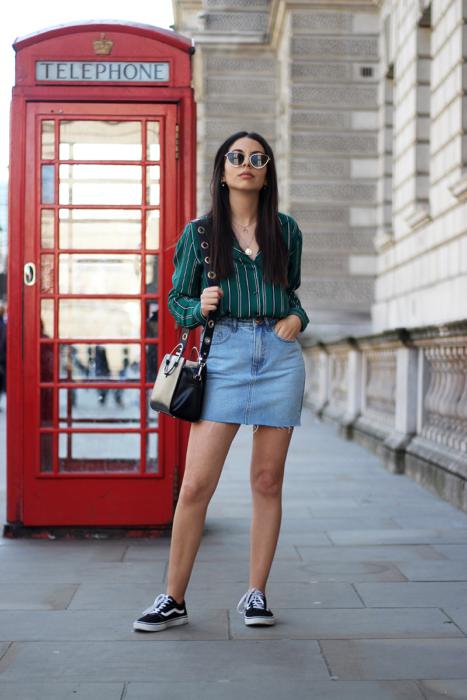 Faldas para el verano; chica de cabello lacio y largo, parada frente a un teléfono rojo de Londres, usando una blusa verde rayada y falda denim