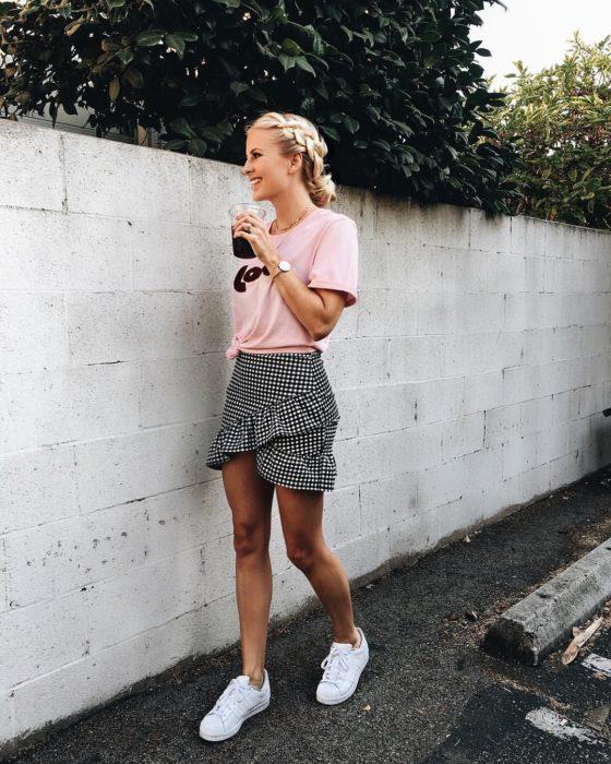 Faldas para el verano; mujer tomando bebida, con peinado de trenza y chongo, con blusa básica rosa y falta de cuadros cruzada