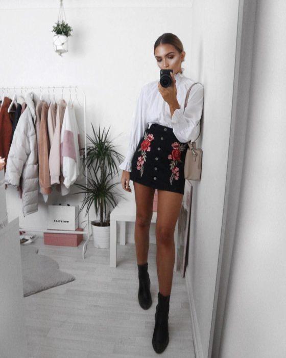 Faldas para el verano; chica tomándose selfie frente al espejo, con blusa blanca, falda negra con rosas bordadas y botines negros
