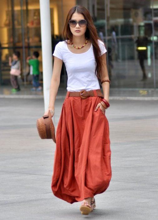 Faldas para el verano; chica caminando en la calle con falda roja, larga y con bolsillos