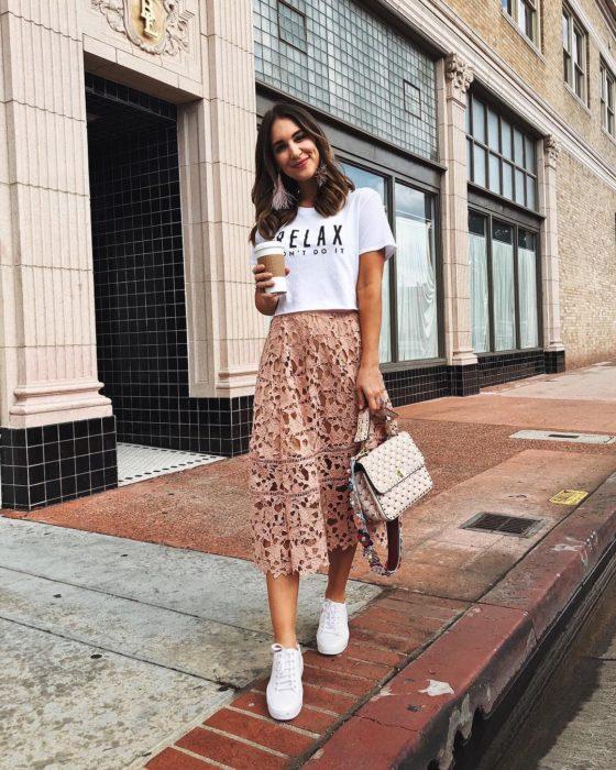 Faldas para el verano; chica caminando en la calle con café en la mano y falda color salmón de encaje
