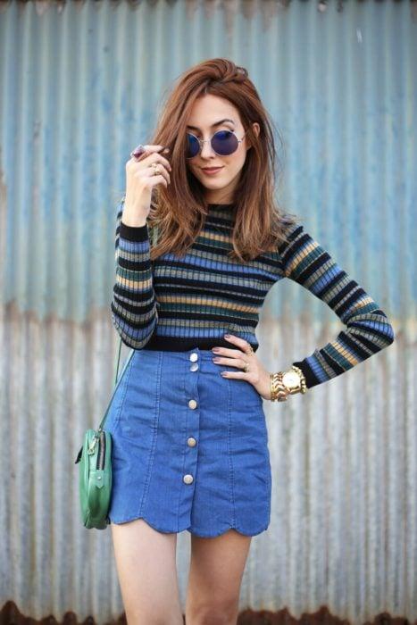Faldas para el verano; chica de cabello castaño y mediano, con lentes de sol redondos, blusa de manga larga rayada y falda denim corta