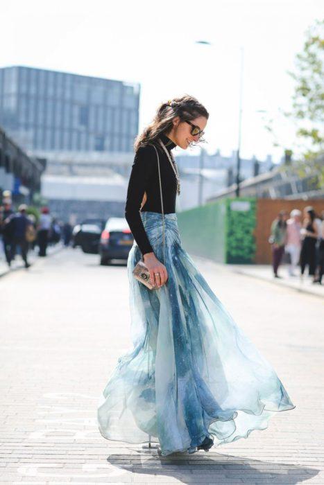 Faldas para el verano; chica con blusa negra de mangas largas y falda de gasa color azul cielo