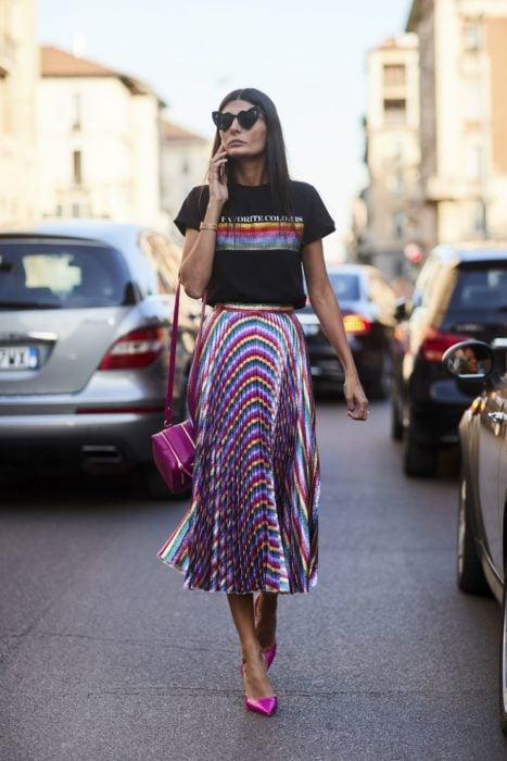 Faldas para el verano; mujer de cabello lacio, con lentes en forma de corazón, camisa casual y falda de satín de colores del arcoíris