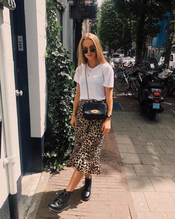 Faldas para el verano; chica rubia con lentes de sol, blusa blanca básica, falda larga de animal print y botas militares Dr. Martens