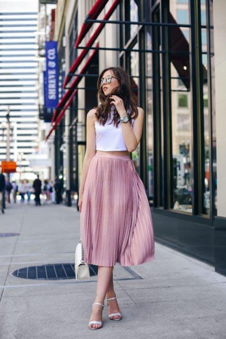Faldas para el verano; chica caminando en la calle, con lentes de sol, top blanco y falda de satín larga color rosa