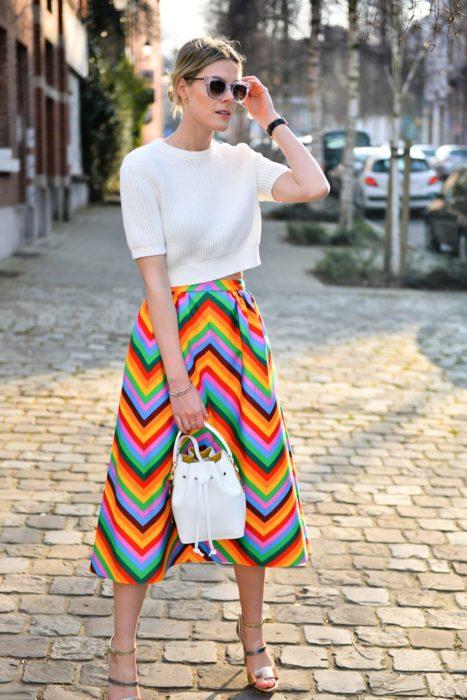 Faldas para el verano; mujer rubia con peinado de chingo, con top blanco de manga 3/4, falda con rayas de colores