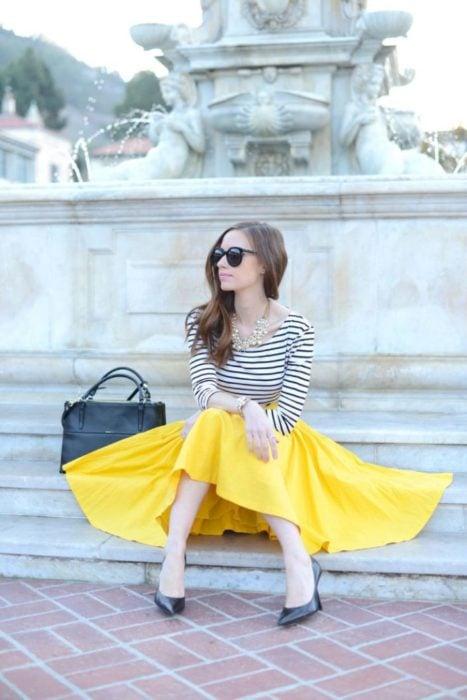 Faldas para el verano; chica sentada en una fuente con vlusa de mangas largas rayada y falda amarilla