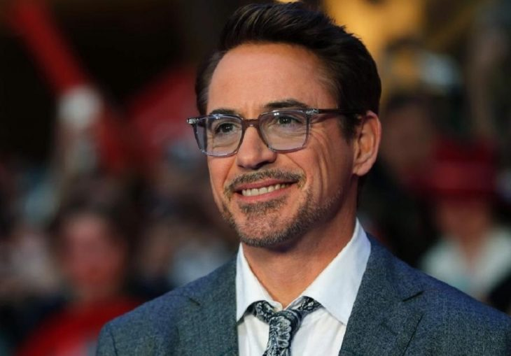 Actor de Iron Man, Robert Downey Jr. con traje gris y lentes de aumento