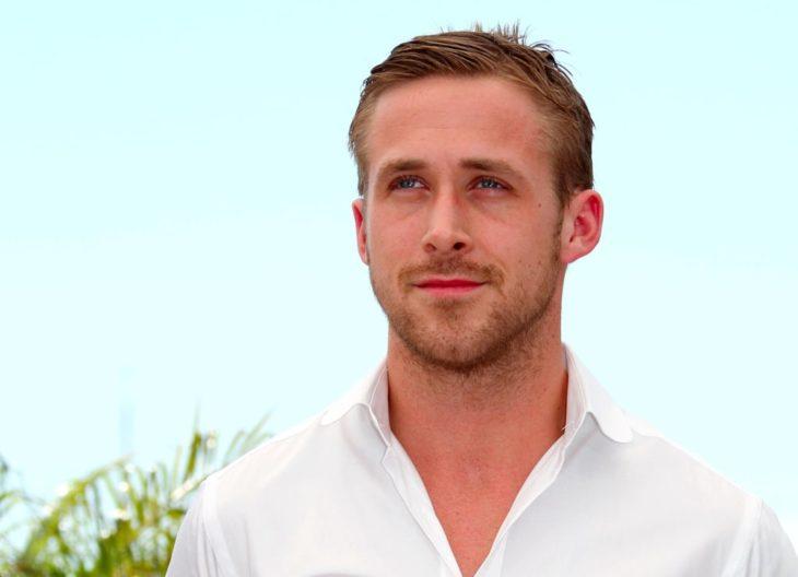 Ryan Gosling con camisa blanca, modelando en la playa