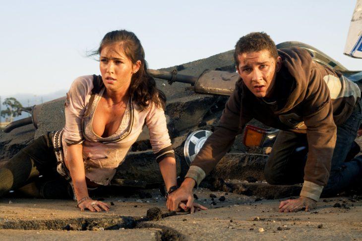 Megan Fox recostada en el piso árido, escena película Transformers