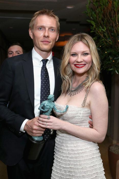 Christian Y Kirsten Dunst sosteniendo un premio