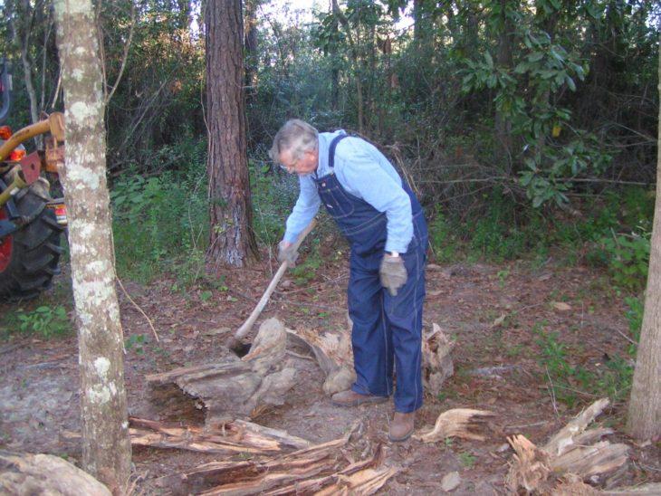 Kenneth Smith, hombre mayor cortando leña con un overol de mezclilla