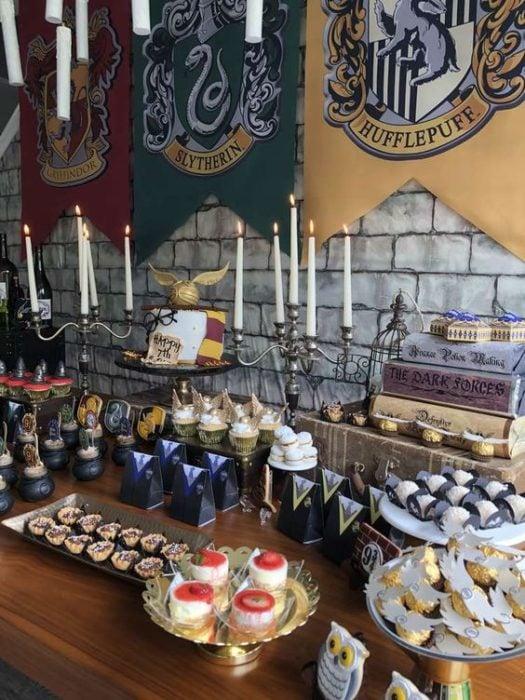 Mesa de dulces con las banderas de las casas mágicas de Harry Potter