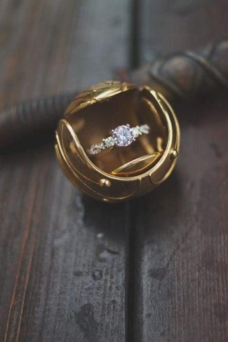 anillo de compromiso dentro de una caja que simula ser una snitch dorada