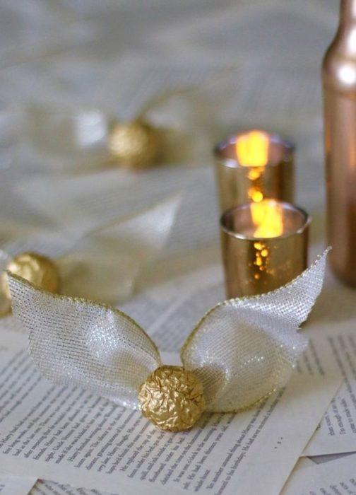 Chocolates con empaque dorado, decorados con alas imitando una snitch dorada