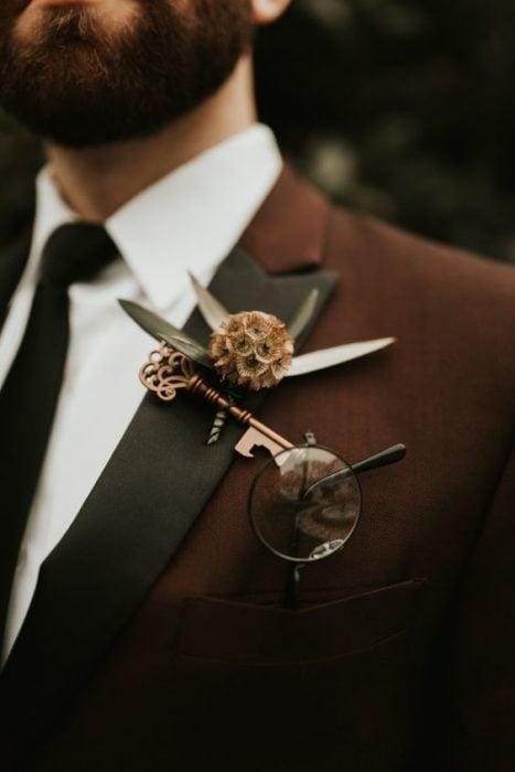 Hombre con traje sastre en color vino y un prendedor en forma de llave inspirado en Harry Potter