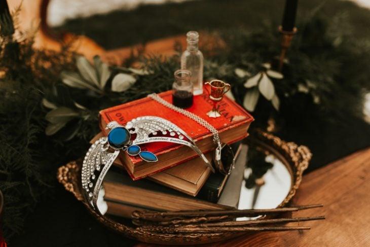 Libro rojo dentro de una cesta de madera inspirado en Harry Potter y las reliquias de la muerte