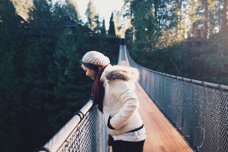 mujer parada en lo alto de un puente