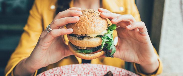 chica comiendo hamburguesa con doble pan