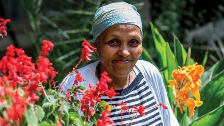 Mamitu Gashe en un jardín entre flores