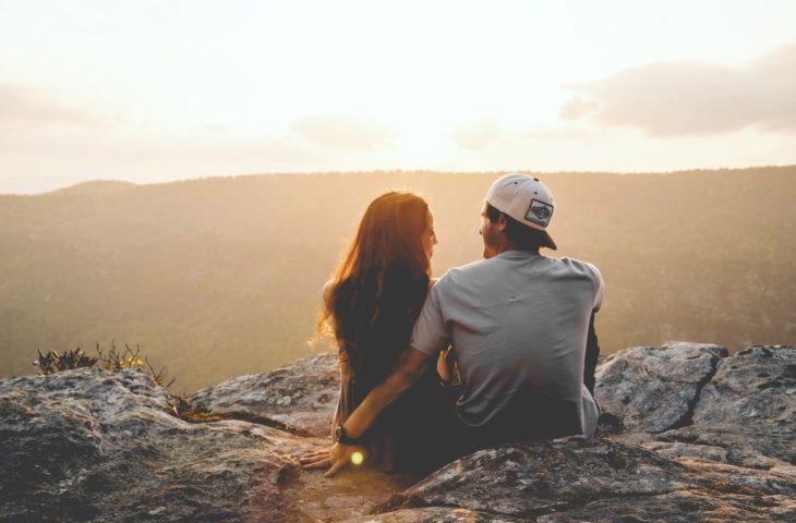 pareja joven sentados en lo alto de una montaña