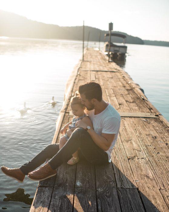 Un hombre y su hija están sentados un un muelle de madera él la besa en la cabeza