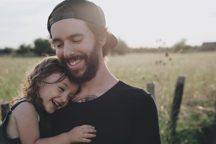 un hombre con cachucha abraza a su niña con el fondo de un campo verde