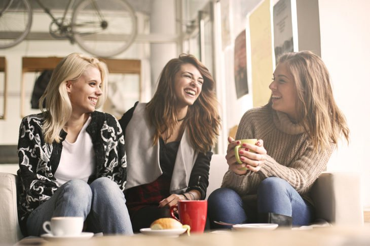 tres mujeres hablan en un café, una sostiene una taza