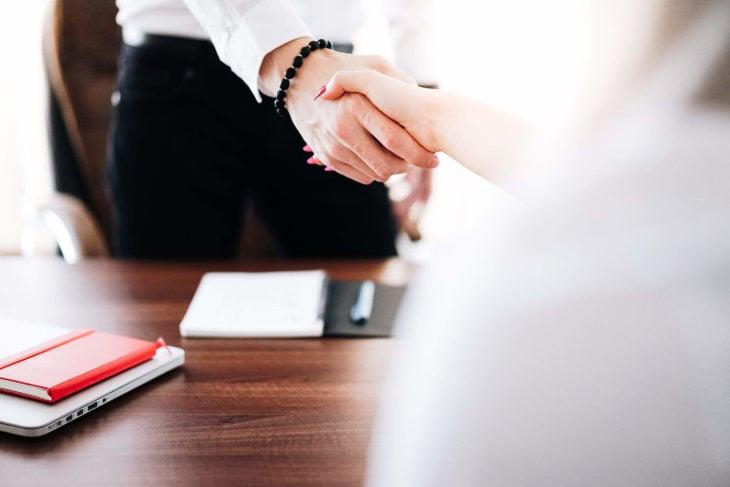 una mujer le da la mano a otra frente a un escritorio