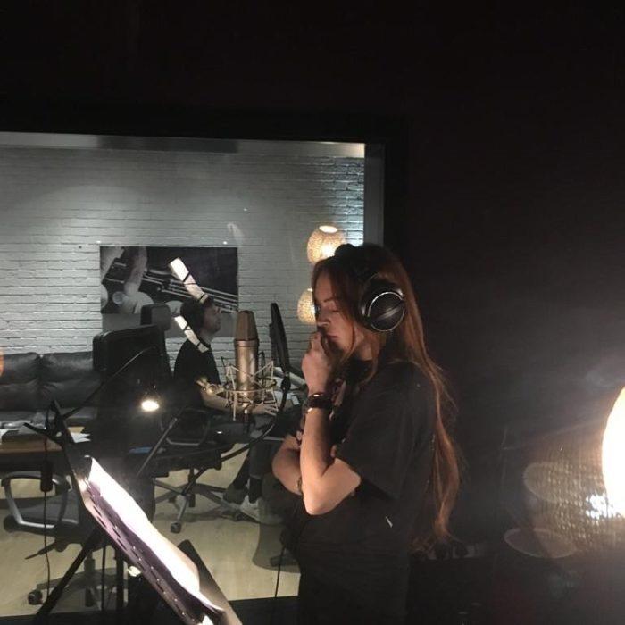 Lindsay Lohan parada frente a un microfono en una cabina de grabación concentrada
