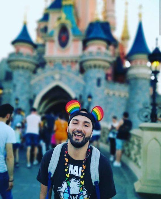 Magical Pride en Disneylandia; chico con barbay cachucha de orejas de Mickey Mouse frente a castillo