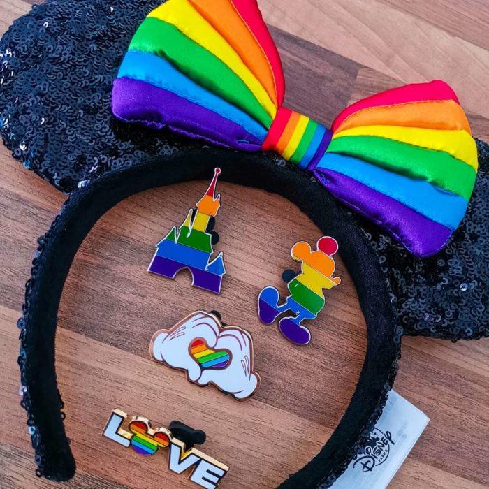 Magical Pride en Disneylandia; recuerdos de Disney con bandera de colores; diadema con orejas de Minnie Mouse y pines de Mickey y castillo